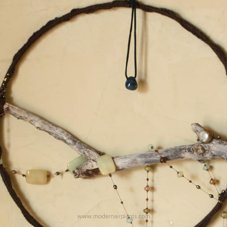weave necklace around hoop and stick
